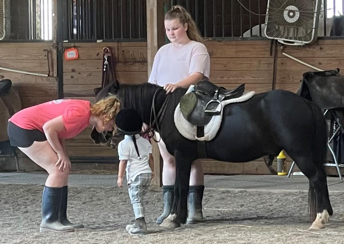 Two instructors with a young pony rider
